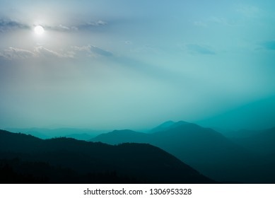 Abstract full blue moon emotinal skyscape. Teal pastels of foggy dream background with soft Tiffany blue to hazy purple sky above mountain tops. Sequoia National Park forested hills in misty light.