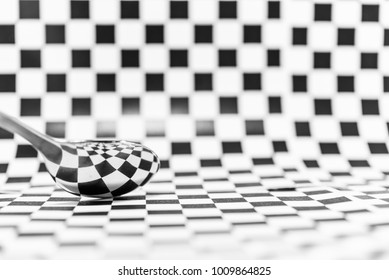Abstract geometric black and white or checkered marble with a reflection of a spoon for background