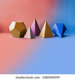 Abstract geometric figures. Three-dimensional dodecahedron pyramid tetrahedron cube rectangular objects on blue pink background. Bright platonic solids still life background. Blank space.