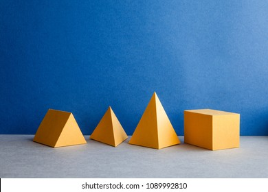 Abstract geometric figures. Three-dimensional pyramid tetrahedron cube rectangular objects on blue gray background. Yellow color Platonic solids still life background..
