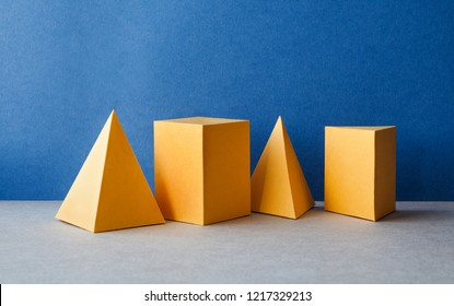 Abstract geometric figures. Three-dimensional pyramid tetrahedron cube rectangular objects on blue gray background. Yellow color Platonic solids still life background.