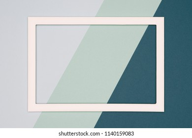 Abstract geometrical cold grey and green colored flat lay paper background. Minimalism template with empty picture frame mock up.