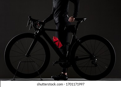 Abstract Girl posing with roadbike. Black bicycle with red water bottle. Side lit cyclist against dark background.