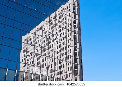abstract of glass skyscraper with reflections of another skyscraper against blue sky