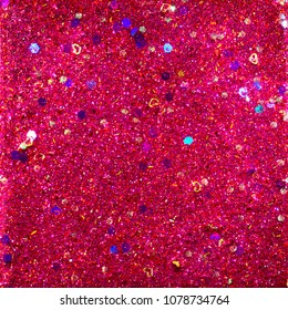 Abstract glitter design with red and purple glitter, gold hearts and holographic chunky pieces for a sparkling background..