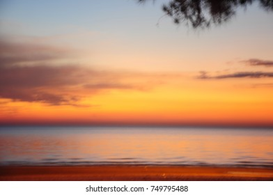 An abstract of glowing and blurry orange color of sunset at the beach.