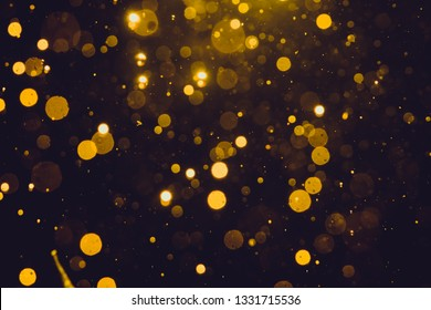 Abstract gold bokeh form water with black background