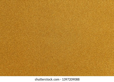 Abstract gold glitter paper texture background or backdrop. Empty shimmer paper or yellow shiny paperboard for design element. Shimmering surface for christmas holiday or new year celebration concepts