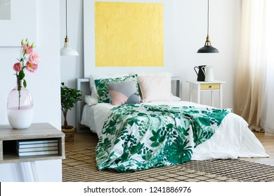 Abstract golden painting on the white wall of trendy bedroom interior with floral bedding on cozy bed and jugs on nightstand