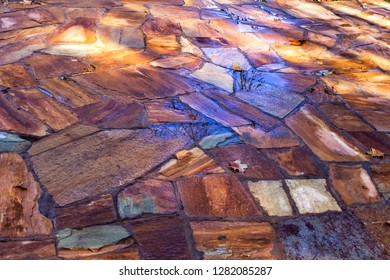 Abstract graphic pattern of sunspot and shadow on wet colored paving slabs