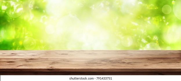 Abstract green bokeh background with empty rustic wooden table for a spring decoration