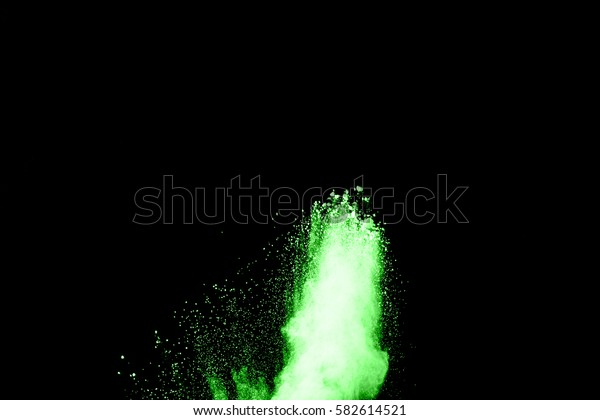 abstract grenn dust explosion on  black background.abstract green powder splatted on black background.Freeze motion of green powder exploding.