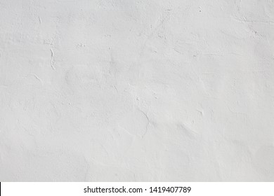 Abstract Grunge White Stucco Wall Background. Old uneven plaster wall of building is painted in white color close up. Rough Texture or Web banner With Copy Space for design