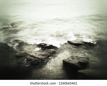 abstract grungy  surrealism art style image of coastline in monochrome black and white color, strong wave splash over the rock at the beach