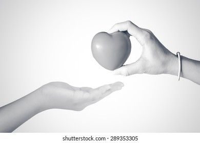 Abstract of hand giving a red heart to hand