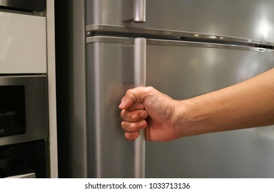 Abstract hand of a man is opening a refrigerator door