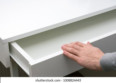 Abstract hand a young man is opening a drawer in the table, background with copy space
