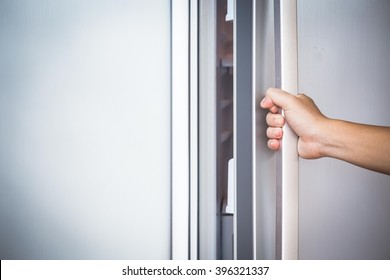 Abstract hand a young man is opening a refrigerator door