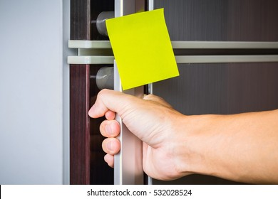Abstract hand a young man is opening a refrigerator door with sticker note for text message.