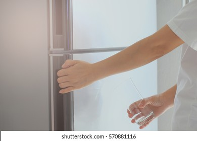 Abstract hand a young woman is opening a refrigerator door