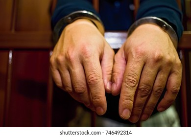 Abstract. Hands of the prisoner on a steel lattice close up. Prison, man in handcuffs. Detail of hands with steel handcuffs.