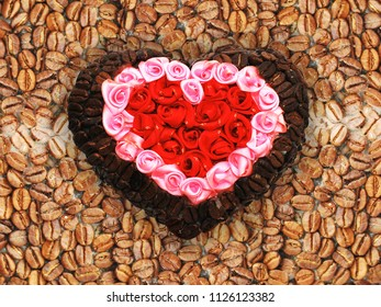abstract heart of artificial rose flowers and coffee beans on the background of coffee beans