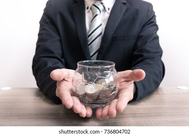 The abstract image of the asian business man hold the coin jar and white background is backdrop. The concept of financial, banking, economizing and investment.