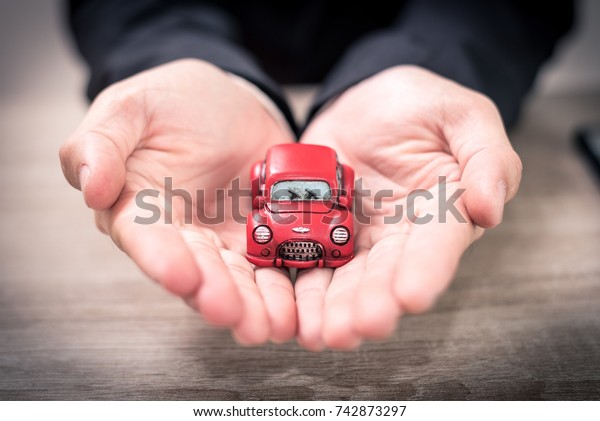 The abstract image of the asian business man hold a toy car on the table. The concept of automobile, property, ownership, insurance and transportation.