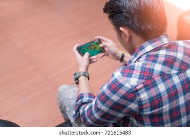 The abstract image of the asian gamer playing video game by the smartphone. the concept of activities, gaming, technology, lifestyle, education, e-sport and internet of things.