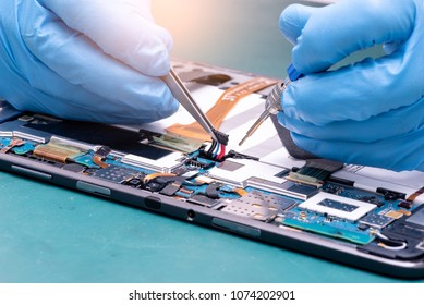 The abstract image of the asian technician assembling inside of tablet by screwdriver in the lab. the concept of computer hardware, mobile phone, electronic, repairing, upgrade and technology.