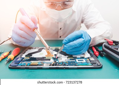 The abstract image of the asian technician repairing a tablet by soldering iron in the lab. the concept of computer hardware, mobile phone, electronic, repairing, upgrade and technology.