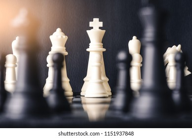 the abstract image of the black and white chess king face to face on the chess board. the concept of strategy, intelligence and education.