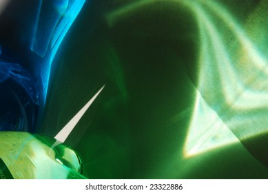 Abstract image of blue and green light refractions on plain paper.