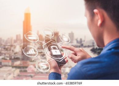 The abstract image of business man point to the hologram on his smartphone and blurred cityscape is backdrop. the concept of communication network cyber security internet of things and internet.
