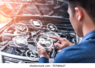 The abstract image of business man point to the hologram on his smartphone and blurred car engine room is backdrop. the concept of communication, network, insurance,  financial and internet of things.