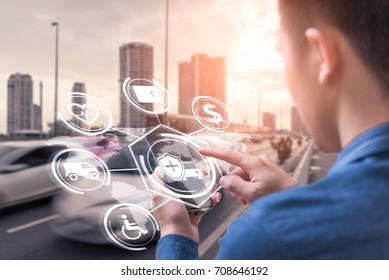 The abstract image of business man point to the hologram on his smartphone and blurred traffic is backdrop. the concept of communication, network, insurance, financial and internet of things.