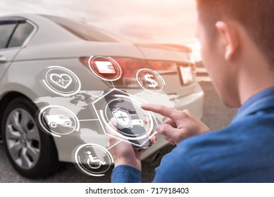 The abstract image of business man point to the hologram on his smartphone and blurred car is backdrop. the concept of communication, network, insurance, financial and internet of things.