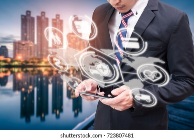 The abstract image of business man point to the hologram on his smartphone and blurred cityscape is backdrop. the concept of communication, network, insurance, financial and internet of things.