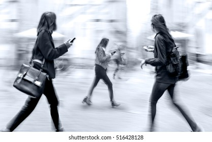 Abstract image of business people on the street talking on a cell phone
