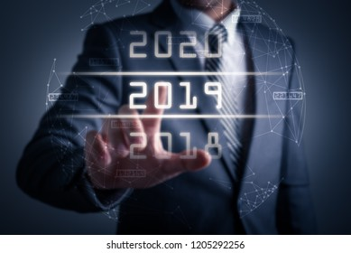 the abstract image of the businessman point to the futuristic years hologram. the concept of new year, futuristic, 2019 and internet of things.