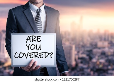 """The abstract image of the businessmen holds a whiteboard and text wrote """"Are you covered?"""" during sunrise overlay with cityscape image. The concept of insurance, business, health care and emergency."""