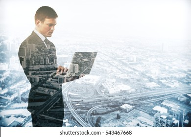 Abstract image of caucasian male using laptop on city background. Double exposure. Communication concept
