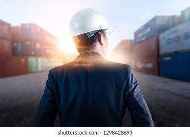 The abstract image of engineer standing in the container yard during sunrise. the concept of engineering, shipping, shipyard, business and transportation.