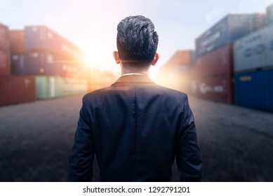 The abstract image of the engineer standing and looking up to the shipping container during sunrise. the concept of engineering, shipping, shipyard, business and transportations.