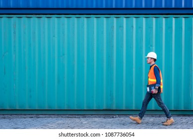 The abstract image of the engineer walking in shipping container yard and copy space. the concept of engineering, shipping, shipyard, business and transportations.