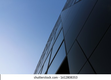 Abstract image of the facade of a modern building covered in reflective plates and glass