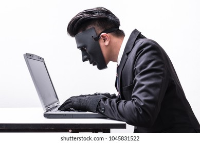 The abstract image of the hacker or programmer wear a mask using a laptop in the empty white room. the concept of cyber attack, virus, malware, illegally and cyber security.