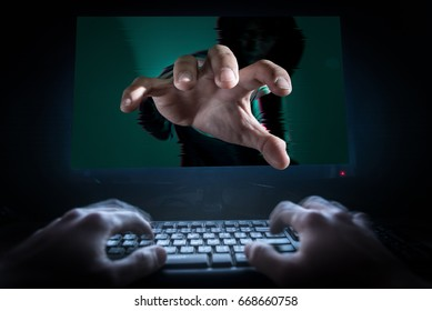 The abstract image of the hacker stretch out one's hand out of the monitor and someone typing on the front. The concept of hacker, cyber security, data theft and data protections.
