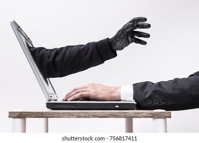 The abstract image of the hacker's hand reach through a laptop screen during business man on typing. the concept of cyber attack, virus, malware, illegally and cyber security.