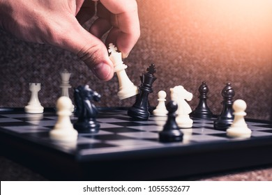 the abstract image of hand take a checkmate on the chess board during the chess game. the concept of strategy, victory, business, win, games, intelligence and education.